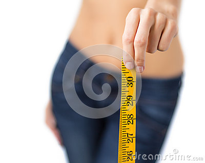 Fit woman confidently showing measurement tape