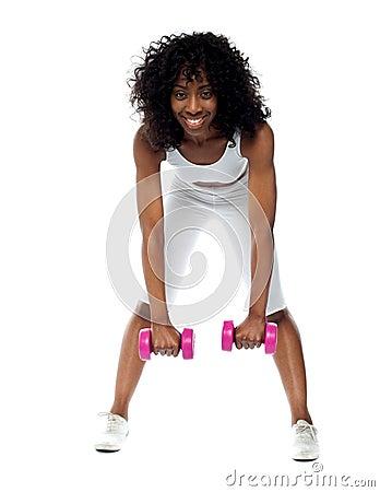 Fit woman exercising. Bending down