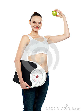 Fit woman holding weighing machine and green apple
