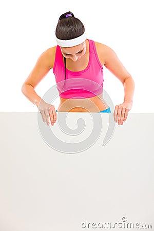 Fit woman in sportswear looking on blank billboard