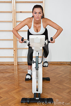 Fit woman on stationary bicycle in gym