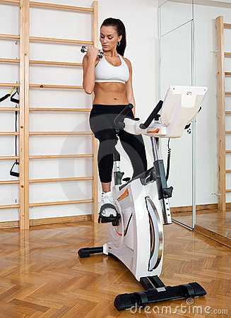 Fit woman working out on stationary bicycle