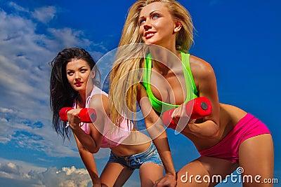Fit women lifting dumbbells