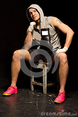 Fit young boxer sitting waiting for a fight
