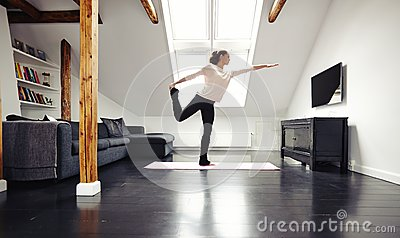 Fit young lady practicing yoga at home warrior pose for Living room yoga timetable