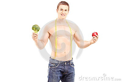 Fit young man holding a fruit and a vegetable