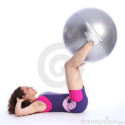 Fit young woman lifts exercise ball with legs
