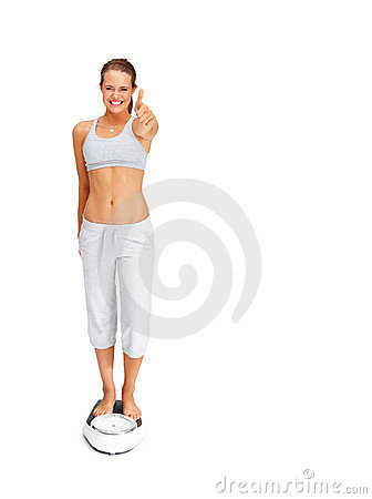 Fit young woman standing on a weighing scale