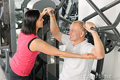 Fitness center trainer assist man exercise back