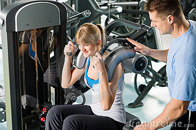 Fitness center young woman exercise with trainer