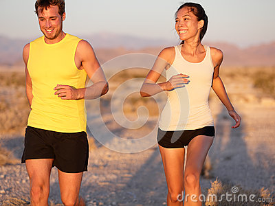 Fitness couple running jogging outside laughing