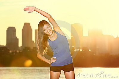 Fitness lifestyle : happy woman stretching in city