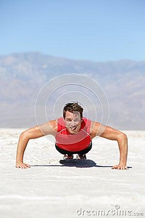Fitness man crossfit training push-ups in desert