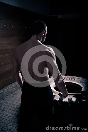 Free Fitness Sledge Hammer Strenght Workout At Gym.Sledgehammer Tire Hits Man Worrking Out At Gym With Hammer And Tractor Tire. Stock Image - 47569561