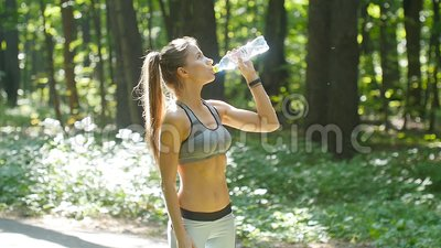 Fitness woman drinking water from bottle in sunny forest. Fitness woman drinking water from bottle outdoors in forest stock footage