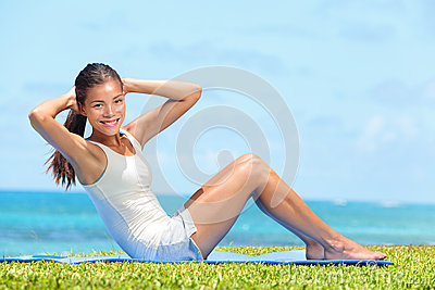 Fitness woman exercising doing sit ups outside