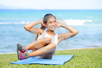 Fitness woman exercising sit ups outside