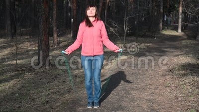 Fitness woman jumping rope. Female is jogging in sunny day light in the autumn trees background, girl training outdoors stock video