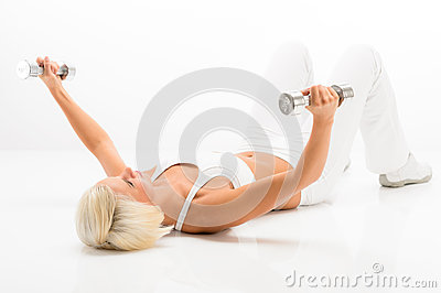 Fitness woman lifting dumbbells lying white floor