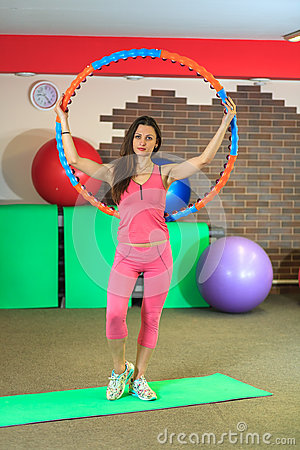 Free Fitness. Young Beautiful White Girl In A Pink Sports Suit Does Physical Exercises With A Hoop At The Fitness Center. Royalty Free Stock Image - 91319446