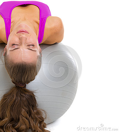 Fitness young woman laying on fitness ball