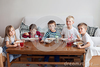 Five adorable kids, eating spaghetti at home Stock Photo