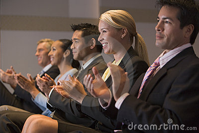 Five businesspeople applauding and smiling