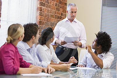 Five businesspeople in boardroom meeting