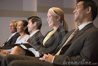 Five businesspeople smiling in presentation