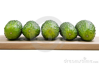 Five cucumbers laying on cutting board