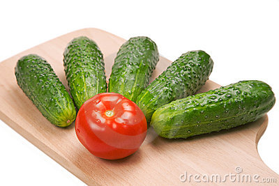 Five cucumbers and one tomato on cutting board