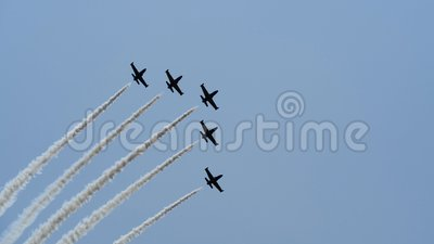 Five exhibition aircrafts are flying and do smoke stunts and drawing at air show. Transport device makes unusual maneuvers and loops. Aircrafts fly through stock video