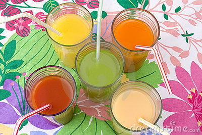 Five glasses of various juices with straws