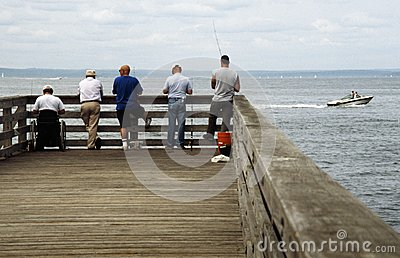 Five men fishing on a pier editorial photography image for Fishing off a pier