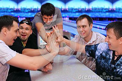 Five men sit at table and touch hands in bowling