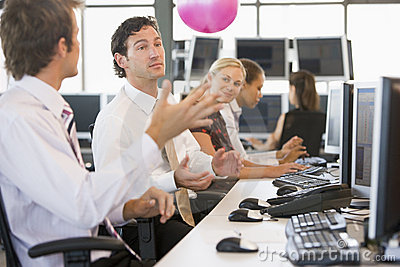 Five people in an office throwing a ball around
