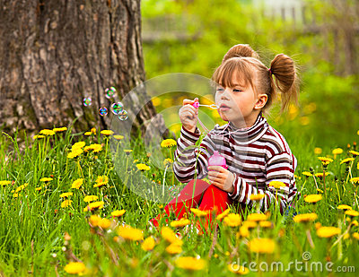 Five-year girl blowing soap bubbles