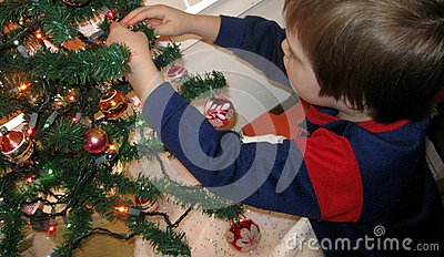 Boy decorating tree
