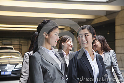 Five young Businesswomen talking and smiling in the parking garage