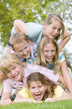 Five young friends piled on each other outdoors