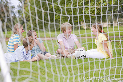 Five young friends on soccer field talking