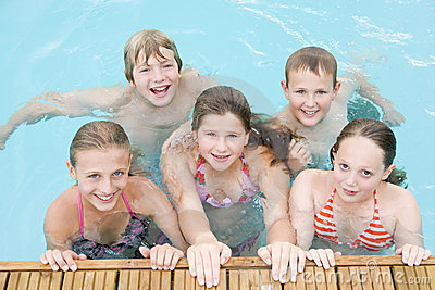 Five young friends in swimming pool smiling