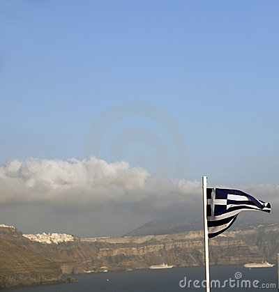 Flag Greece flying over caldera Oia Santorini