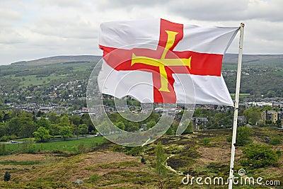Flag of Guernsey over British landscape