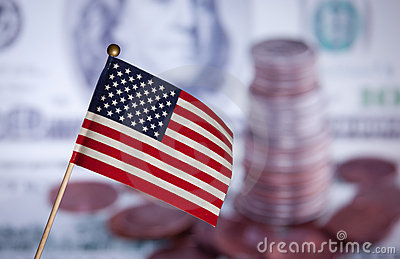 Flag over US dollars banknotes and coins.