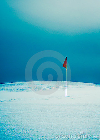 Flag on snowy golf course