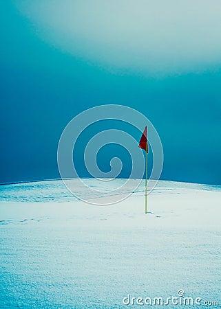 Flag on snowy golf course
