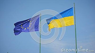 Flagge von Ukraine und Flagge der Europäischer Gemeinschaft flatternd auf einem Hintergrund eines blauen Himmels stock video