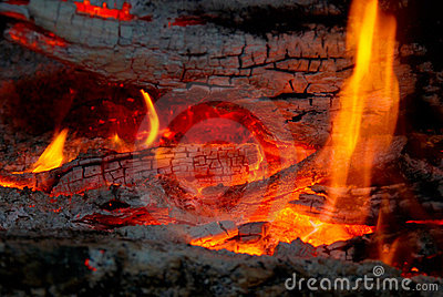 Flame tips on the firewood.
