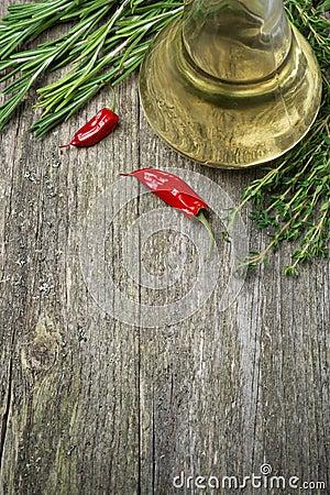 Flaska av olivolja och örter på en träbakgrund